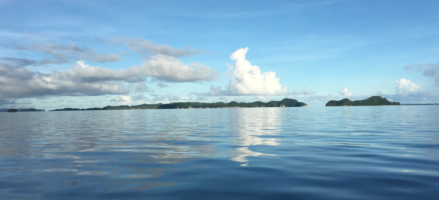 Rock Islands in Palau with clouds reflected in the calm water