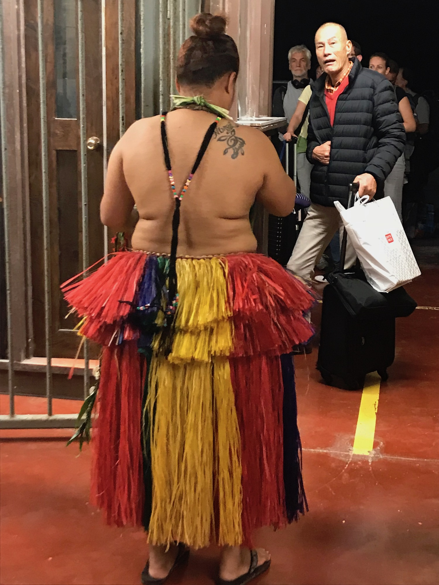 Woman in grass skirt greets visitors at Yap airport