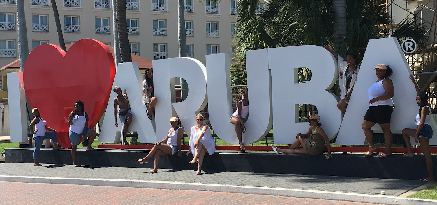 Bachelorettes posing at a massive I Heart Aruba sign